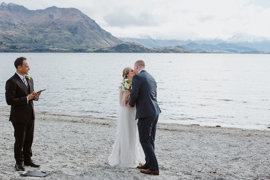 The first kiss!! A gorgeous couple share their first moment as husband and wife beside Lake Wanaka, with photography by Alpine Image Company